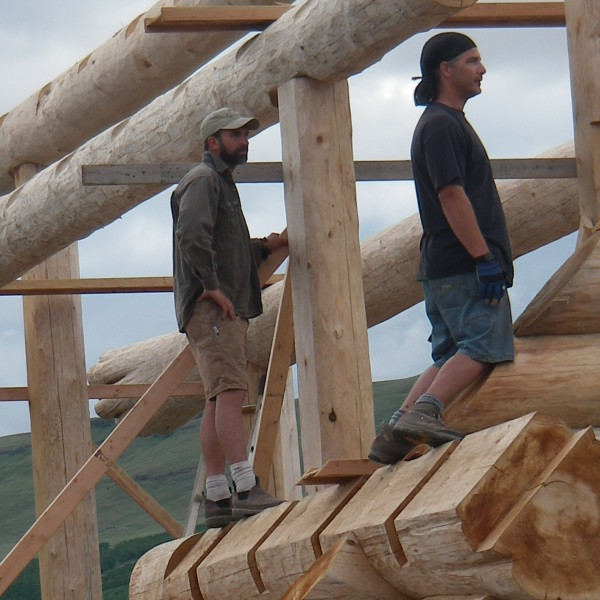 two men on top of logs in new construction of a log home